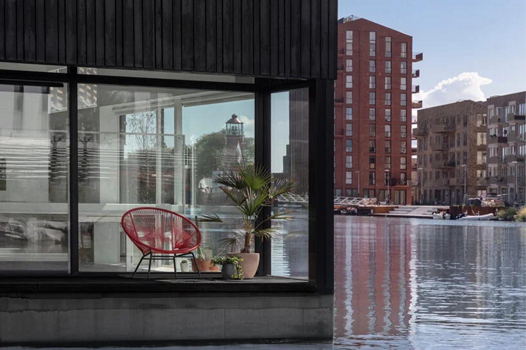 Этот угловой деревянный дом в устойчивой плавучей деревне Амстердама использует электрическую сеть причала для получения чистой энергии!
