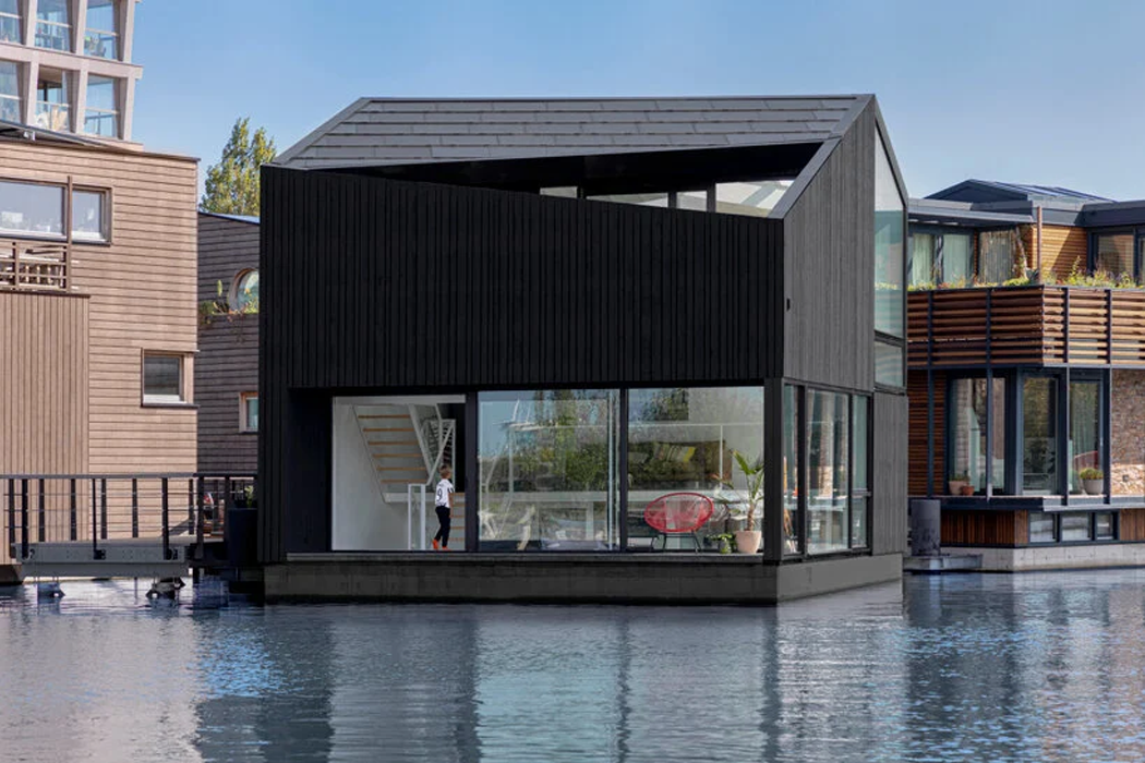 This angular timber home in Amsterdam's sustainable floating village uses the jetty's power grid for clean energy!