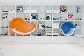 The bookshelf integrating seating nooks makes this renovated basement the ideal summer escape!